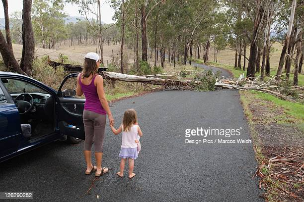a woman and young girl outside their vehicle on the road that is blocked by a fallen tree