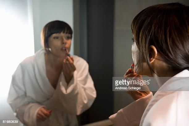 a woman applying lip gloss in a mirror
