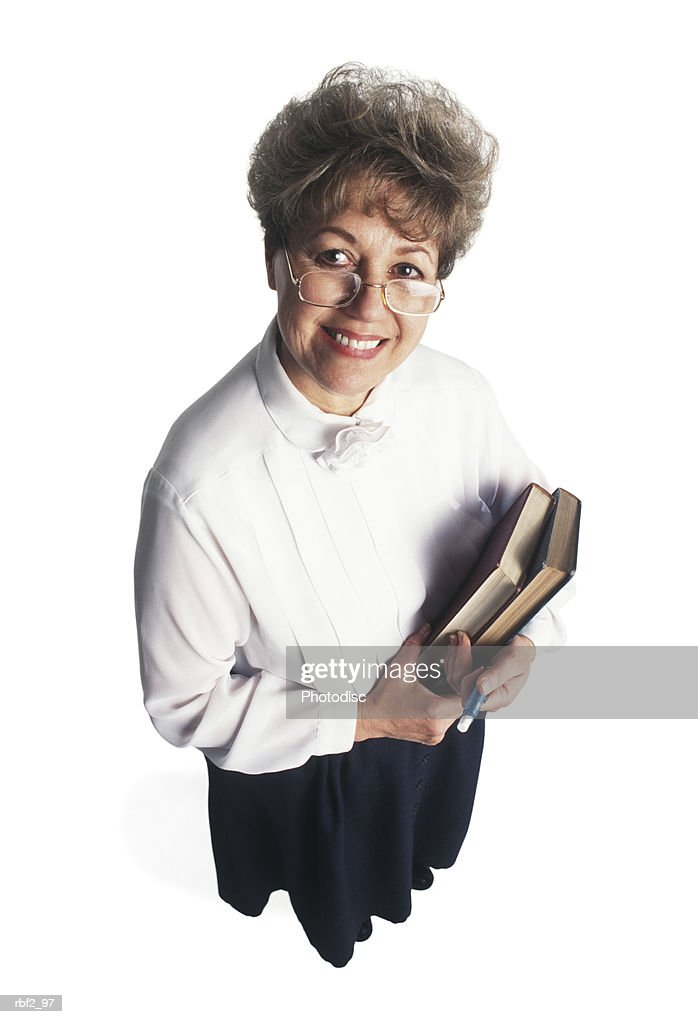 a woman dressed in a black dress and white shirt holds books as she looks up toward the camera : Stockfoto