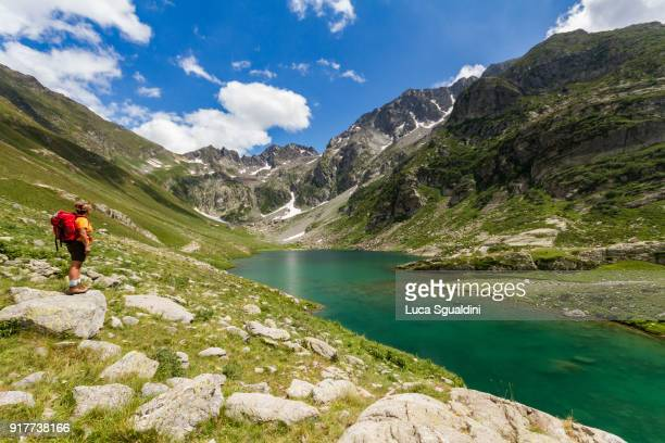 a woman hikes the path along the vej del bouc lake, in the maritime alps natural park. - alpes maritimes stock pictures, royalty-free photos & images