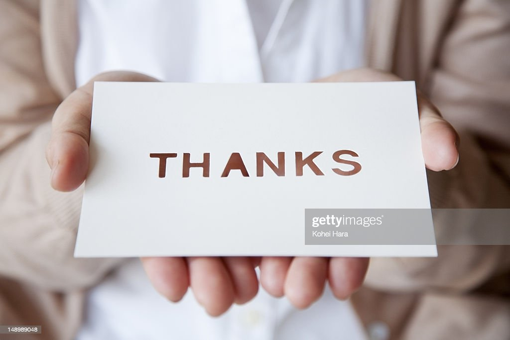 a woman holding a card : Stock Photo
