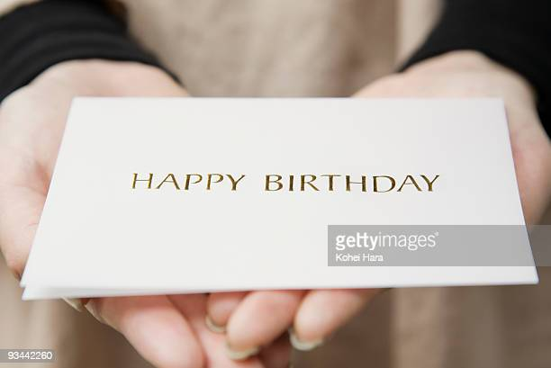 a woman holding a message card - birthday card stock pictures, royalty-free photos & images