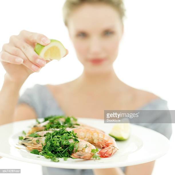 a woman holding a plate of shrimp and squeezing a wedge of lemon over it
