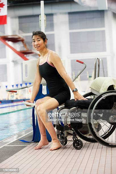 a woman in a wheelchair moves onto a lift on the edge of a swimming pool