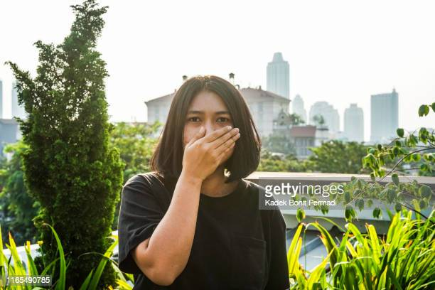 a woman is covering her nose with her hand - unpleasant smell stock pictures, royalty-free photos & images
