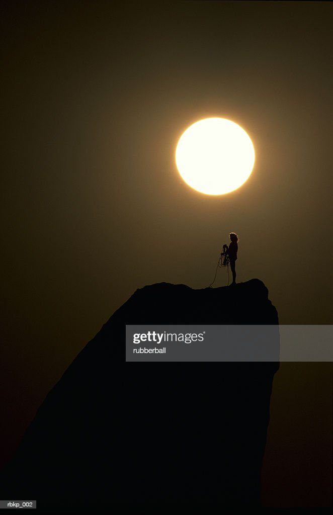a woman is standing on top of a rock formation coiling her rope with the sun setting behind her casting a silhouette : Stockfoto