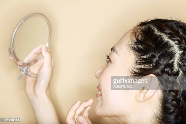 a woman looking at the mirror