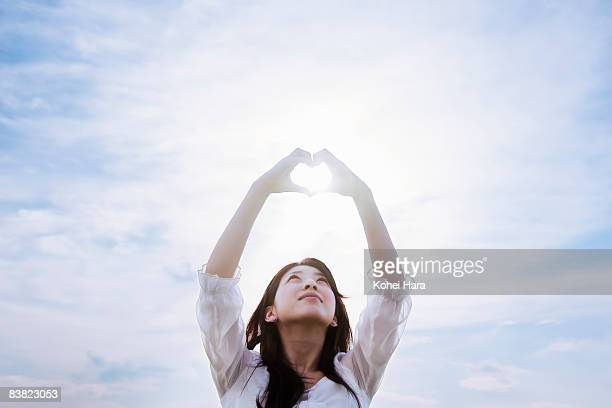 a woman making a heart by hands under a sky