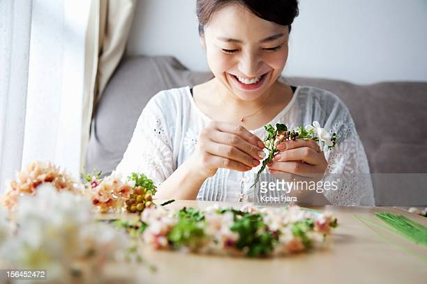 a woman making artificial flowers into corolla