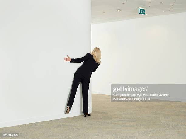 a woman peering around a corner