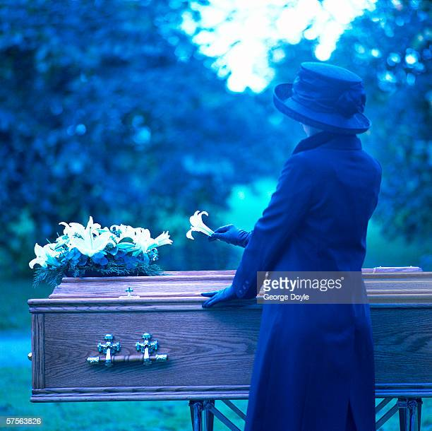 a woman placing a flower on a coffin