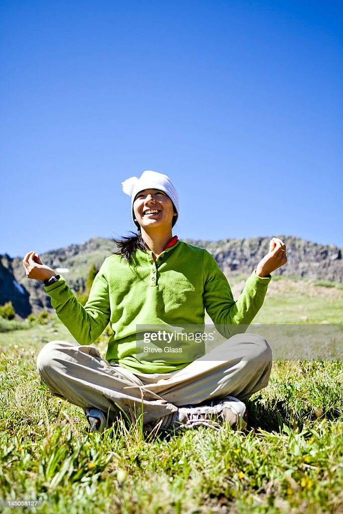 a woman smiles as she sits cross legged in an alpine meadow with wildflowers doing a Buddha pose. They are just off the Continental Divide Trail (CCT, trail number 813) just north of Squaw Pass at approximately 11,840 feet. : Stock Photo