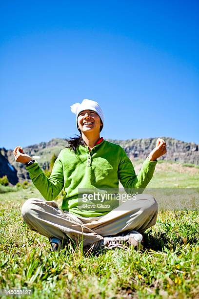 a woman smiles as she sits cross legged in an alpine meadow with wildflowers doing a Buddha pose. They are just off the Continental Divide Trail (CCT, trail number 813) just north of Squaw Pass at approximately 11,840 feet.