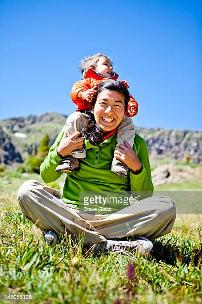 a woman smiles as she sits cross legged in an alpine meadow with wildflowers doing a buddha pose. her son, a 2 year old, crawls on her. they are just off the continental divide trail, cct, trail number 813, just north of squaw pass. - 1歳以上2歳未満 ストックフォトと画像
