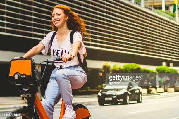 uma mulher sorrindo enquanto andava de bicicleta na cidade de são paulo - ciclismo - fotografias e filmes do acervo