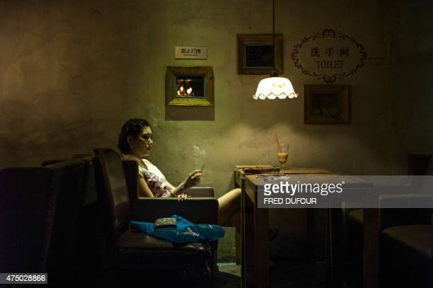 a woman smokes a cigarette in a bar on May 27 2015 in Beijing China's capital seeks to snuff indoor smoking on June 1st 2015 with a new ban and...
