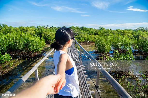 POV of a woman stood on a bridge holding hands and looking into the distance