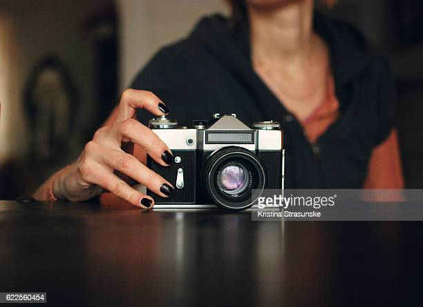 a woman taking photo with a vintage camera