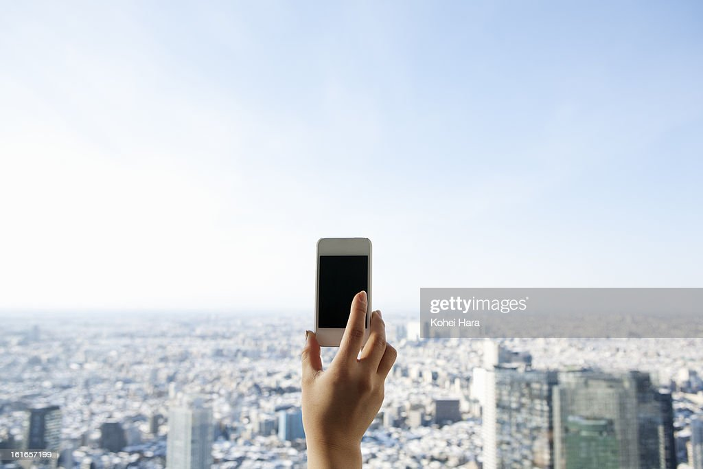 a woman using a smart phone in a skyscraper : Stock Photo