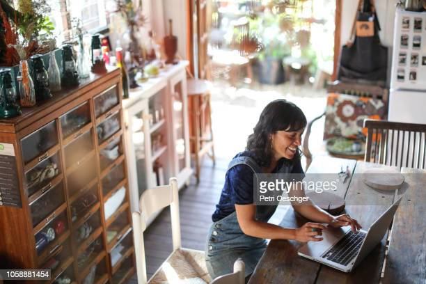 a woman using her laptop in her kitchen at home. - business owner stock pictures, royalty-free photos & images