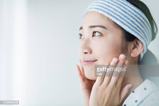 a woman using skin care products - body care and beauty stock pictures, royalty-free photos & images