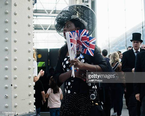 A woman wearing a fascinator and clutching Union Jack flags at Waterloo station, returning from a day at the Royal Ascot races