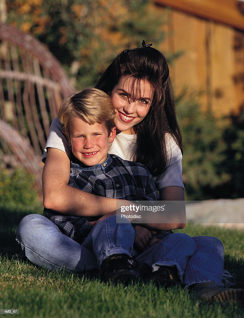 a woman wearing a white shirt and jeans holds a young boy wearing a plaid shirt and jeans in her arms as they sit on green grass : Stockfoto