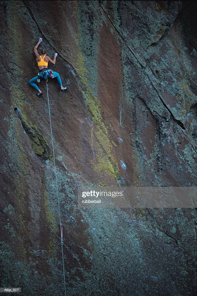 a woman with blue pants and a yellow sports bra is climbing the sheer face of a cliff : Stockfoto