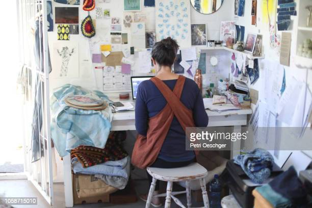 a woman working on her laptop in her home studio. - administrative professional day stock pictures, royalty-free photos & images