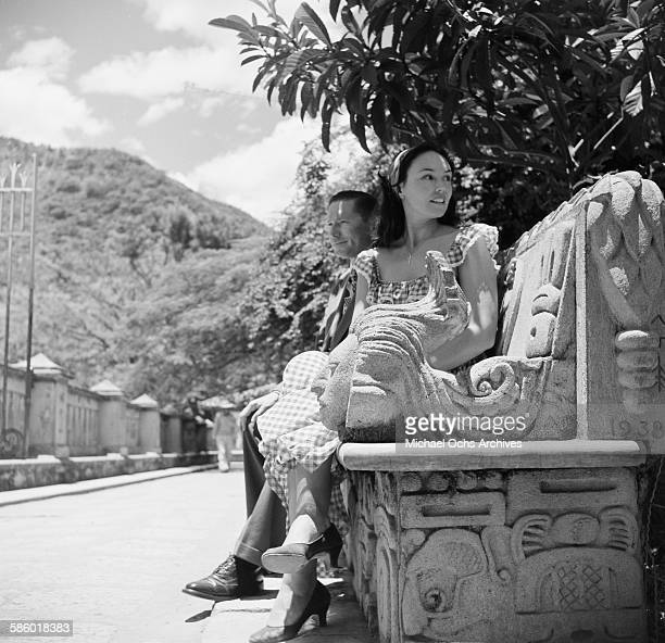 a women sits on a highly sculptured decorated bench in La Concordia Park in Tegucigalpa Honduras