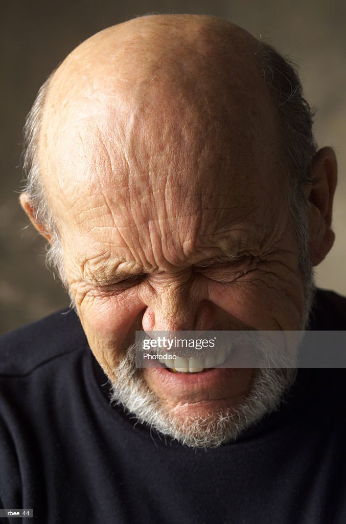 a wrinkle faced balding elderly man wearing a dark shirt scrunches up his face while closing his eyes and grimacing : Stock Photo