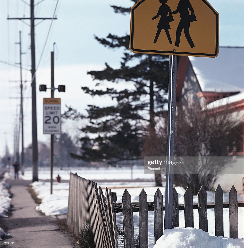 a yellow crosswalk sign rises in front of a snow covered house and evergreen as houses and trees rise in the background : Foto de stock