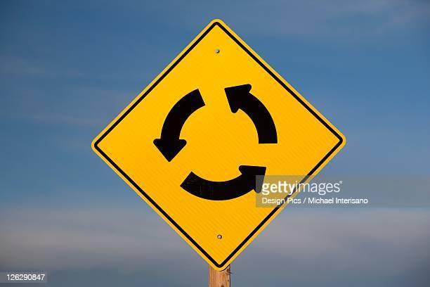 a yellow traffic sign with three arrows going in a circle