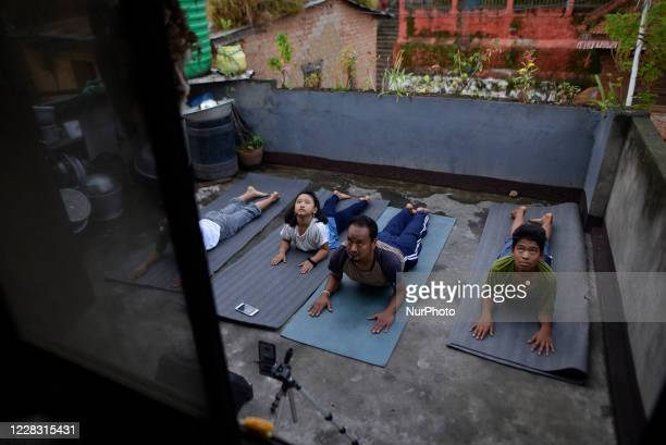 A Yoga Practitioner along with his family members practicing Yoga Positions in the roof of house after the three district administrations have...