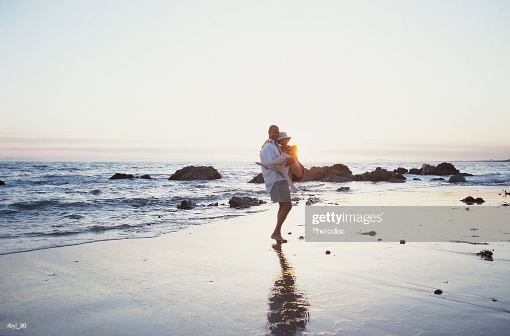 a youing man is carrying a young woman in his arms on a rocky beach at sunset with the ocean behind them : Foto de stock