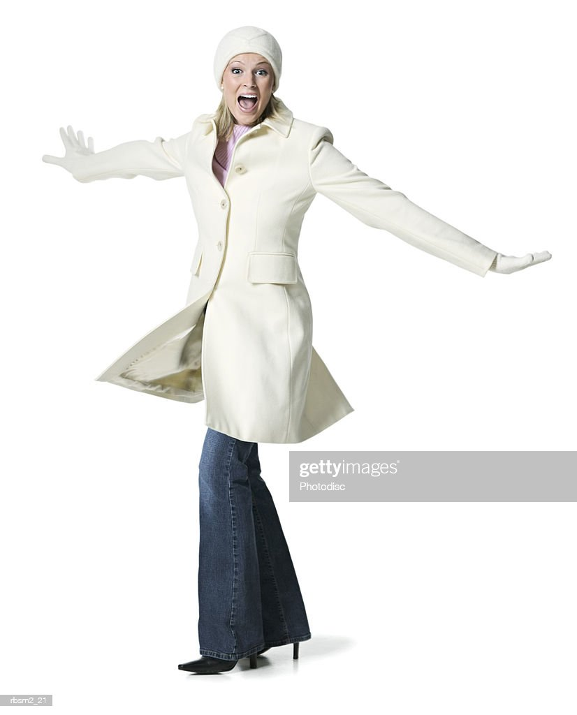 a young adult blonde female in a white winter coat and gloves spins around playfully : Foto de stock