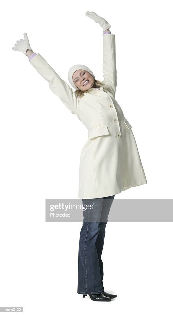 a young adult blonde female in a white winter coat and gloves tosses up her arms and smiles : Foto de stock