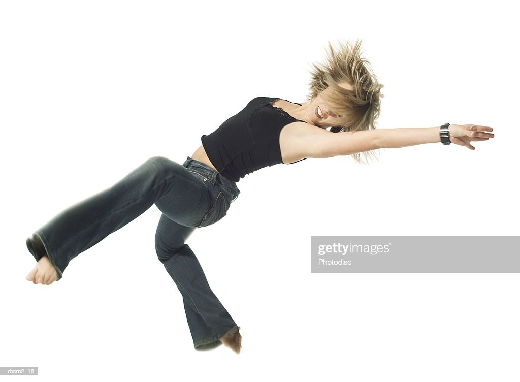 a young adult blonde female in jeans and a black shirt jumps and spins through the air : Foto de stock