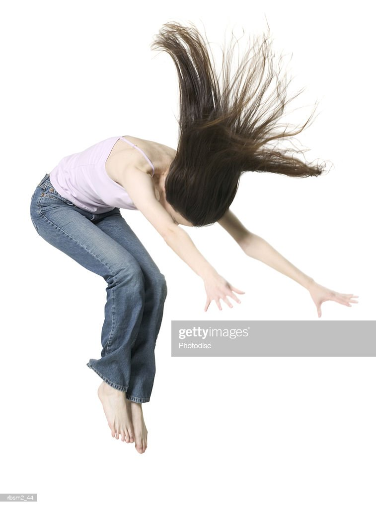 a young adult brunette female in jeans and a pink tank top jumps up into the air : Foto de stock
