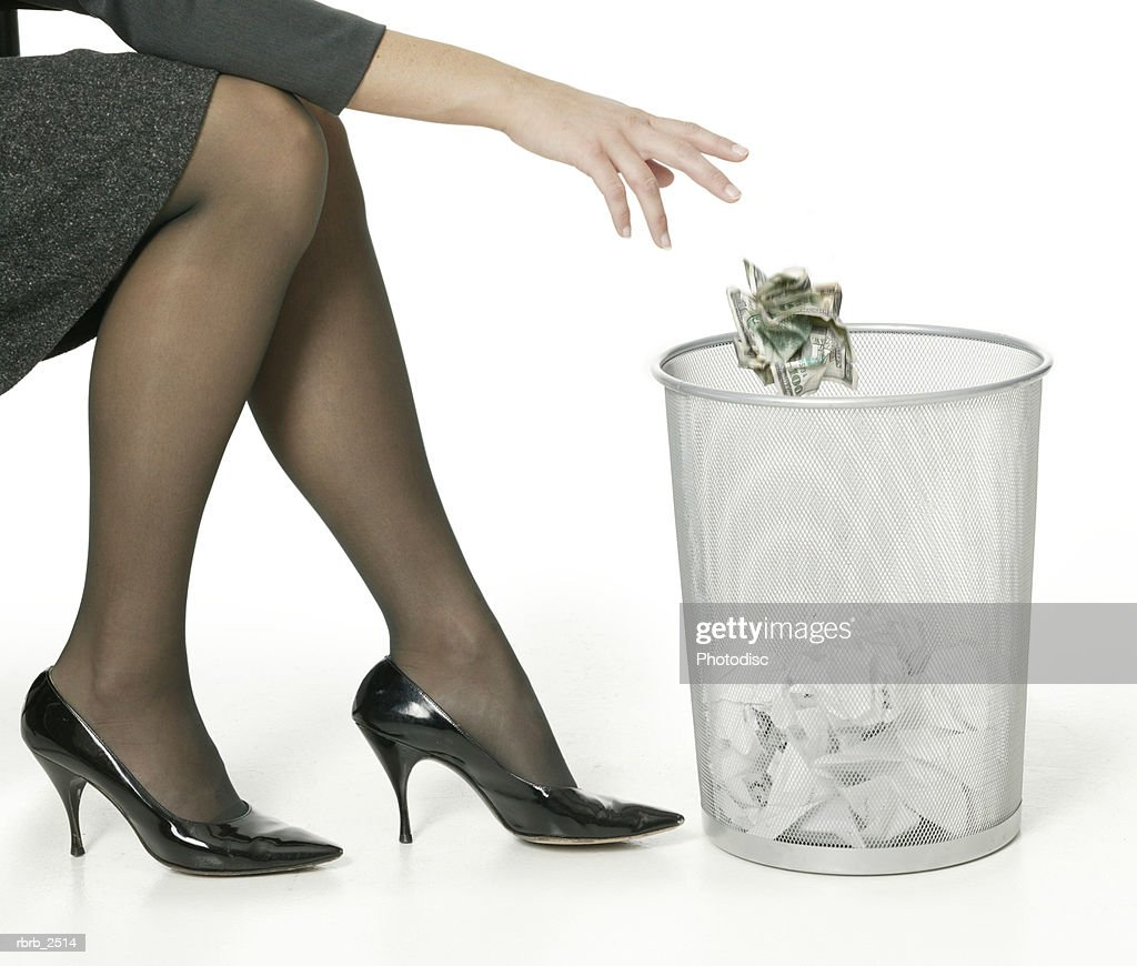 a young adult business woman shows her legs as she tosses away some trash : Foto de stock