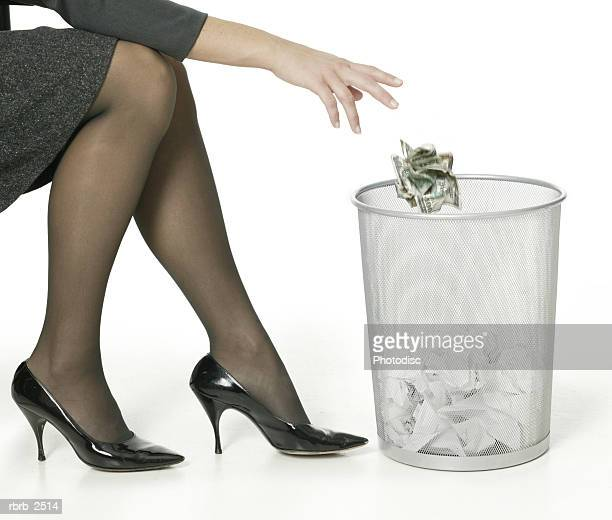 a young adult business woman shows her legs as she tosses away some trash