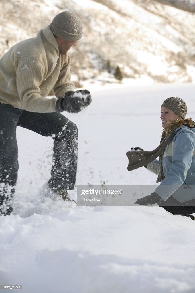a young adult couple in winter clothing play around by having a snowball fight : Stockfoto
