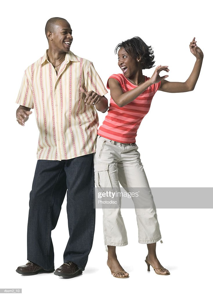 a young adult couple shake and dance together playfully : Foto de stock