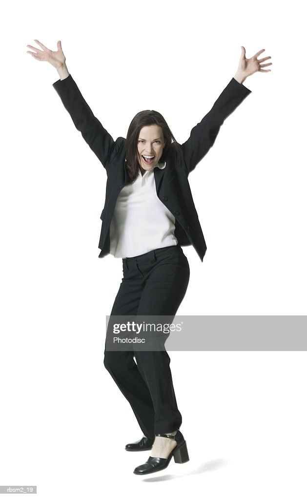 a young adult female in a dark pant suit throws up her arms and smiles playfully : Foto de stock