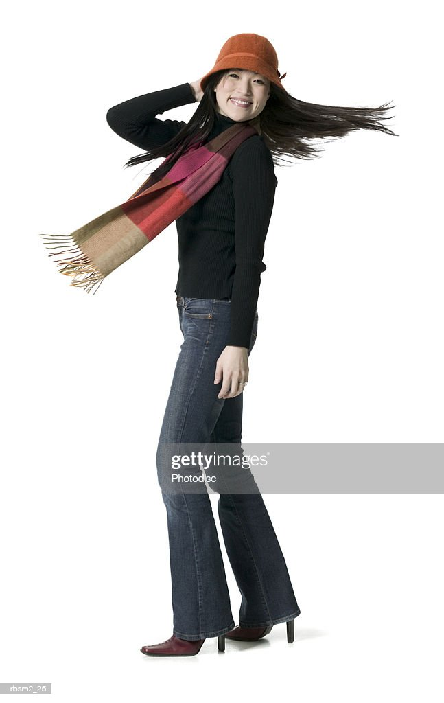 a young adult female in a hat and scarf spins around playfully : Foto de stock