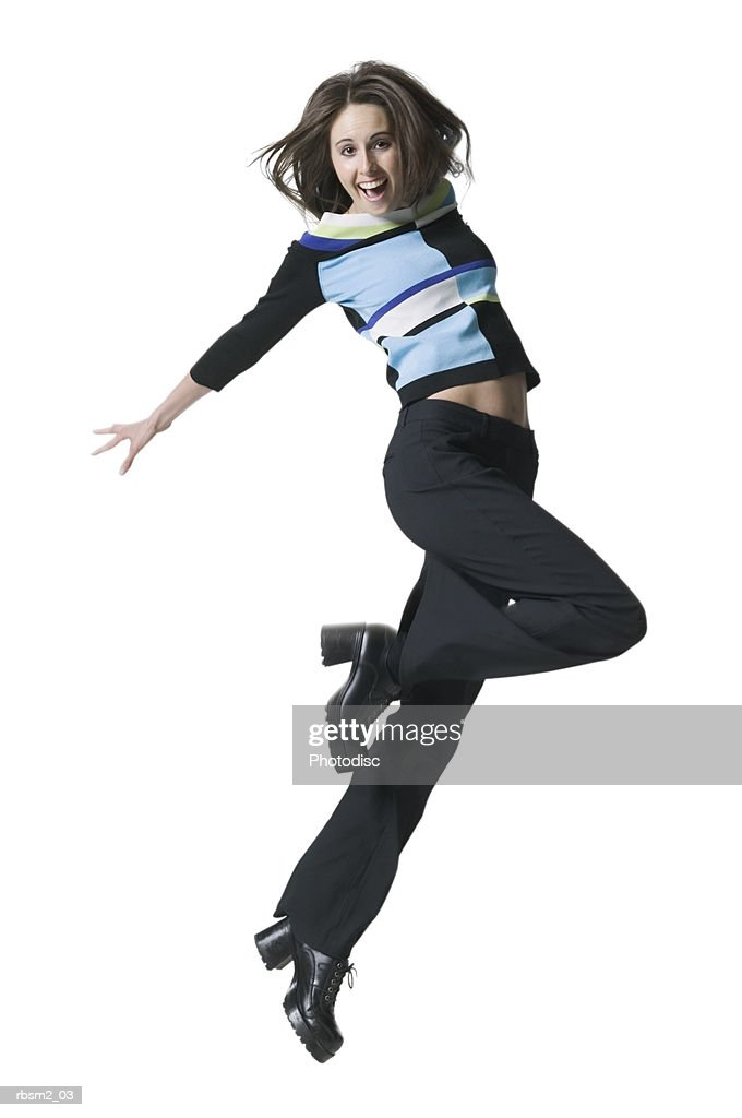 a young adult female in black pants and a colorful sweater jumps through the air : Foto de stock