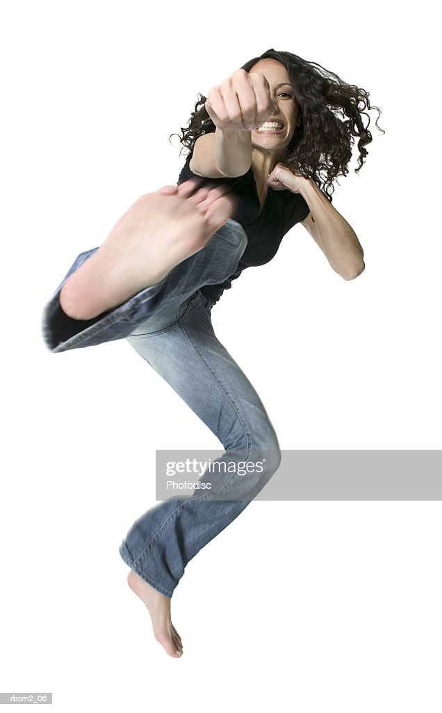 a young adult female in jeans and a black shirt wildly jumps and kicks forward : Foto de stock