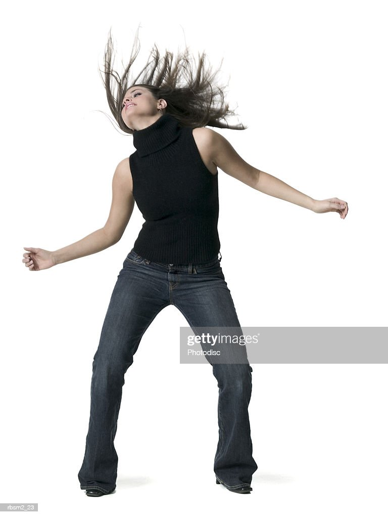 a young adult female in jeans and a black sweater dances and tosses her hair wildly : Foto de stock