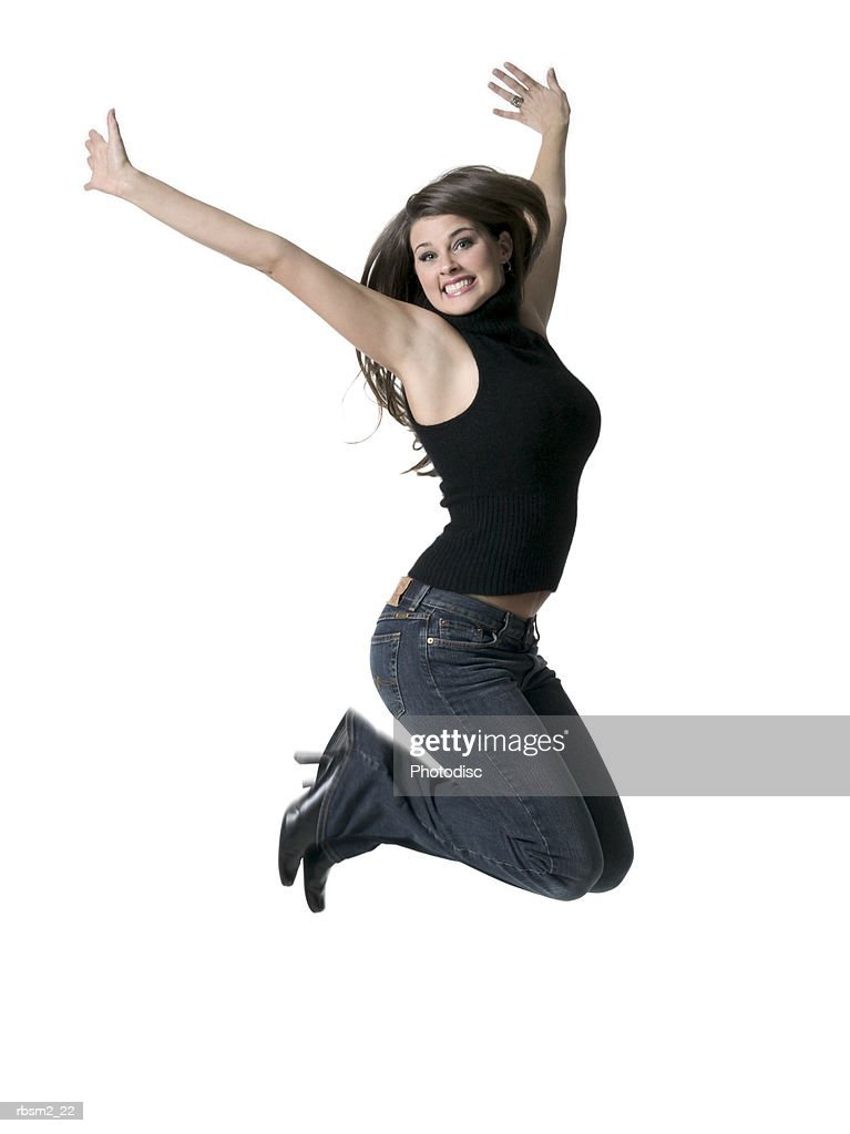 a young adult female in jeans and a black sweater jumps up in the air and smiles : Foto de stock