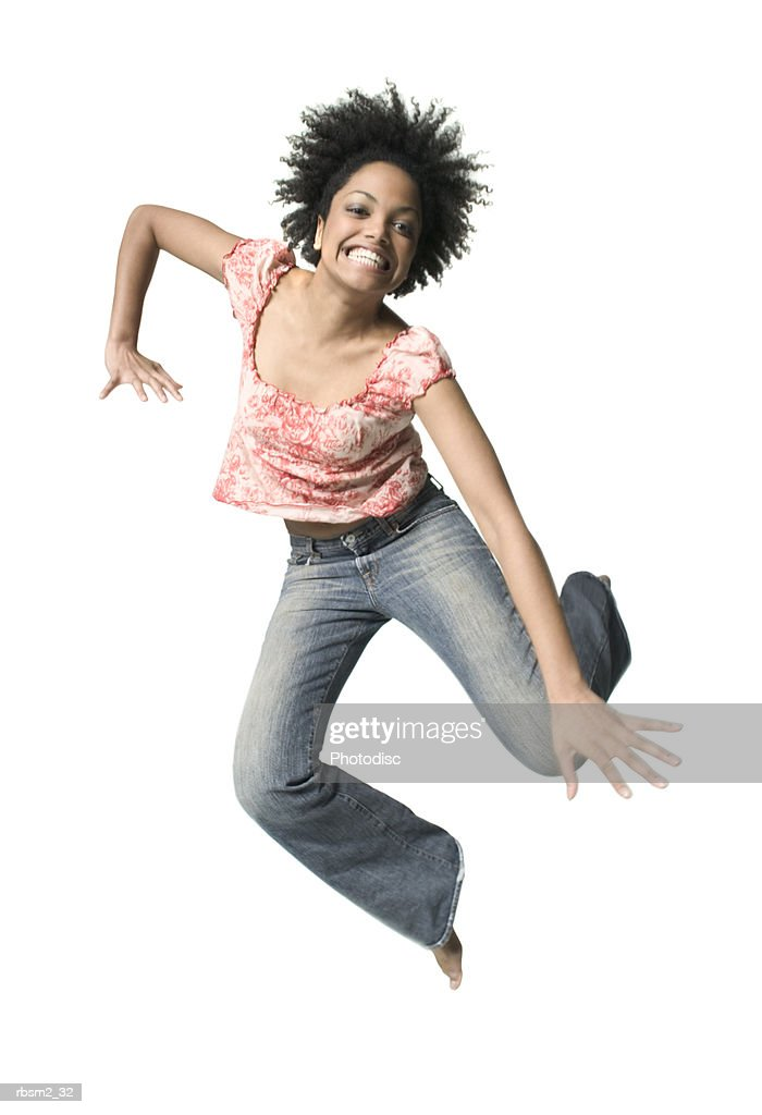 a young adult female in jeans and a floral shirt jumps up playfully : Foto de stock